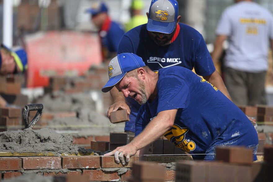 Nathan Milster maintains a frantic pace during the fourth annual regional Bricklayer 500 on September 12, 2019, while mason tender Adrian Enriquez helps prepare bricks and mortar.