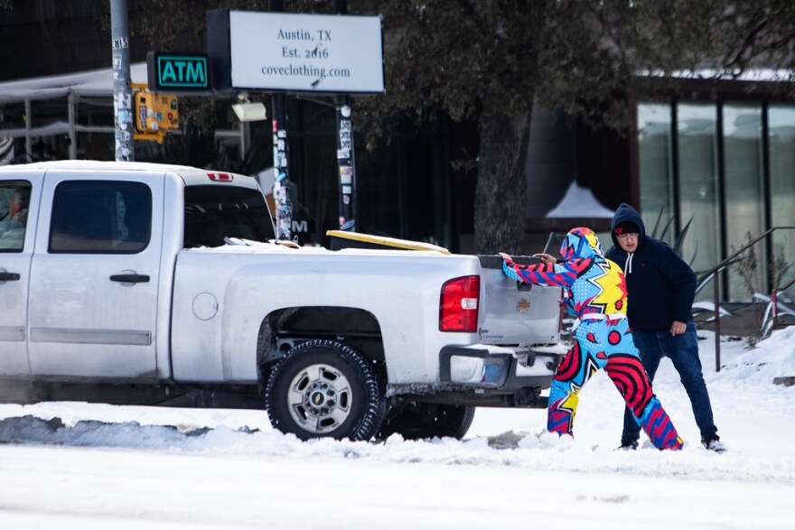 People try to push a truck out of the snow on South Congress Avenue on Monday.
