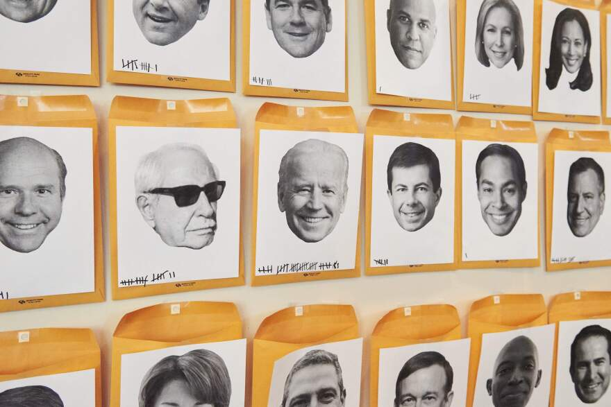 """A wall titled """"Who's The Next To Drop Out?"""" with faces of the Democratic candidates running for president in the 2020 election is displayed during the Netroots Nation conference at the Pennsylvania Convention Center in Philadelphia on Saturday."""