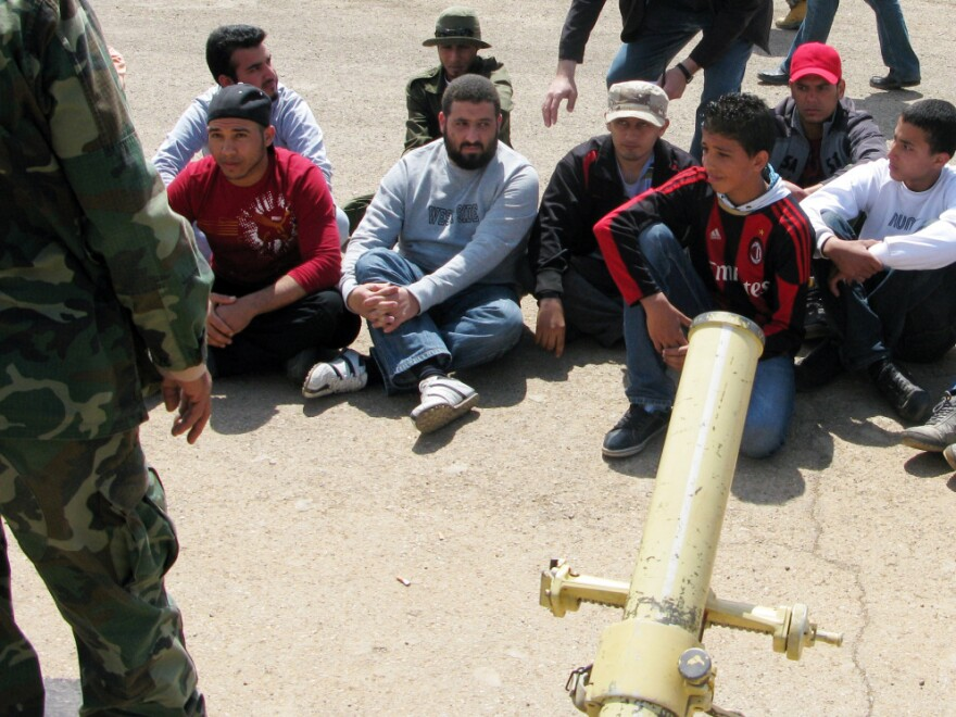 Ihab Budabuus (front, second from right) and other recruits are learning with live fire in the cement lot of a military base in Benghazi.