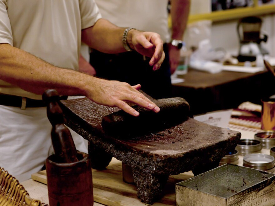 A Mars Inc. employee demonstrates how cacao beans are ground into cocoa powder at a chocolate-making demonstration at the National Archives.