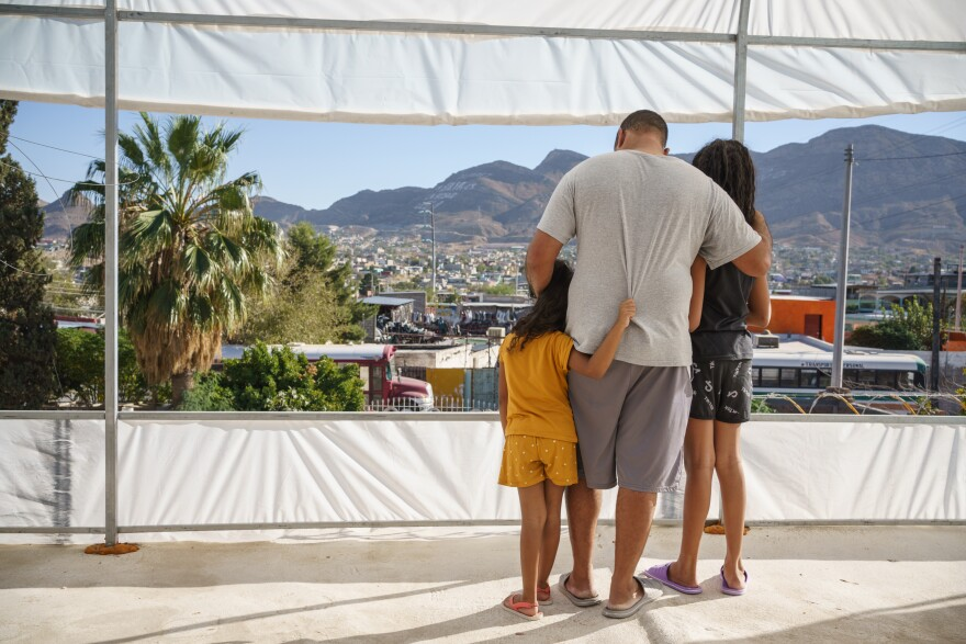 With their backs facing the camera, Carlos wraps his arms around his two daughters as he looks down at his youngest.