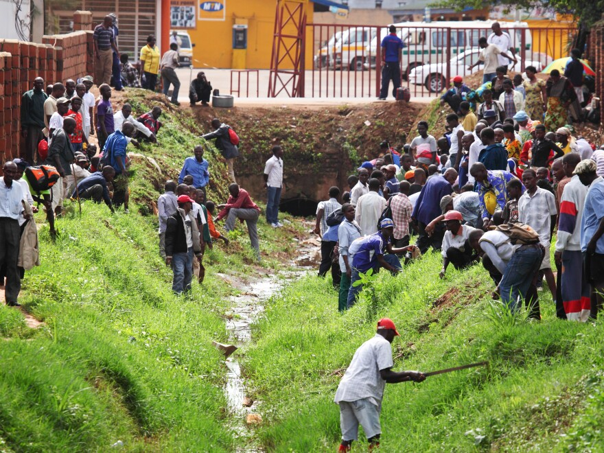 The people of Rwanda are required to take part in the national cleanup day, Umuganda, on the last Saturday of every month. (Above) Getting grass under control in Kigali, the capital city.