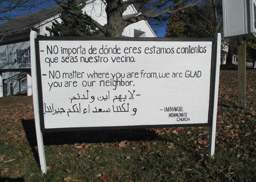 The original black-and-white wooden sign at Immanuel Mennonite in Harrisonburg, Va., has inspired thousands of yard signs. It was written by Pastor Matthew Bucher and translated with the help of congregation members and friends.