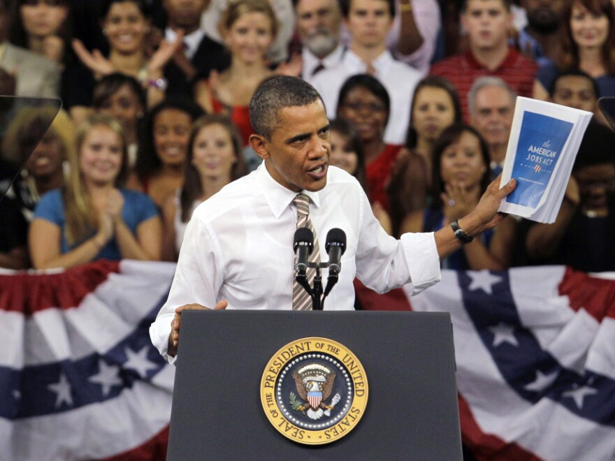 <p>President Obama holds up his jobs bill as he speaks at North Carolina State University in Raleigh, N.C., on Sept. 14. The president returns to North Carolina on Monday to drum up support for his proposals and for his re-election campaign.</p>