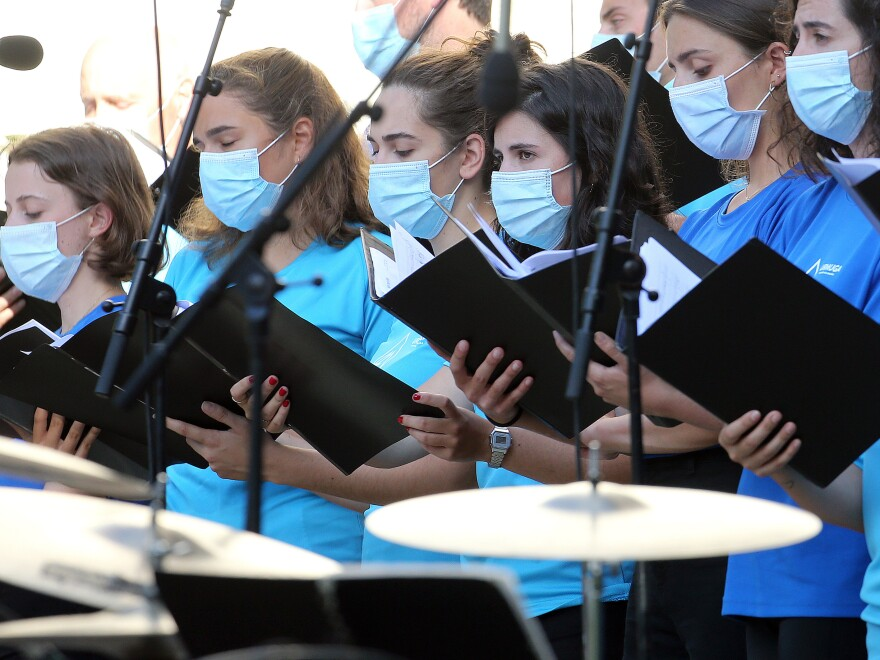 The Centers for Disease Control and Prevention briefly posted new guidance to its website stating that the coronavirus can commonly be transmitted through aerosol particles, which can be produced by activities like singing. Here, choristers wear face masks during a music festival in southwestern France in July.