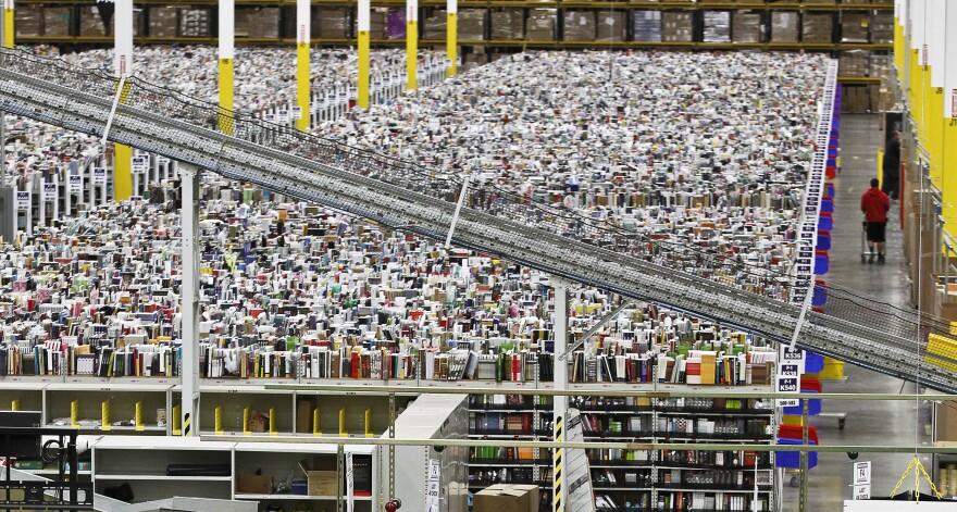 An employee walks through an aisle at Amazon.com's 1.2 million-square foot fulfillment center in Phoenix, Ariz., in November 2012.