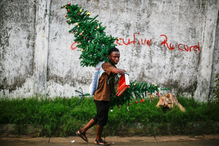 A man peddles plastic Christmas trees and lights in downtown Monrovia.