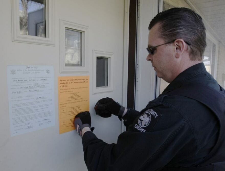 Cook County Deputy Sheriff Scott Hunter posts the final eviction notice on an apartment in Evanston, Ill., Tuesday, March 17, 2009.