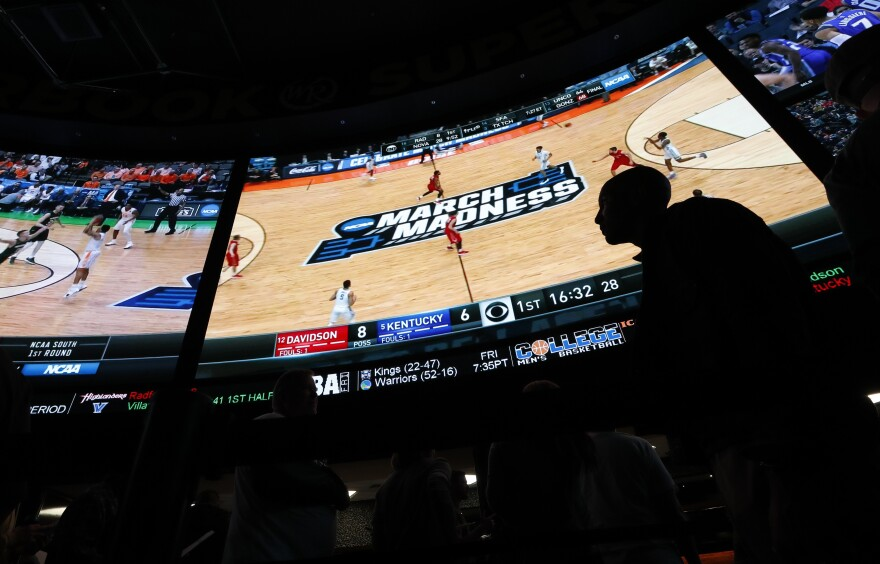 People wait in line to bet on the NCAA college basketball tournament at the Westgate Superbook sports book Thursday, March 15, 2018, in Las Vegas. Sports Betting.