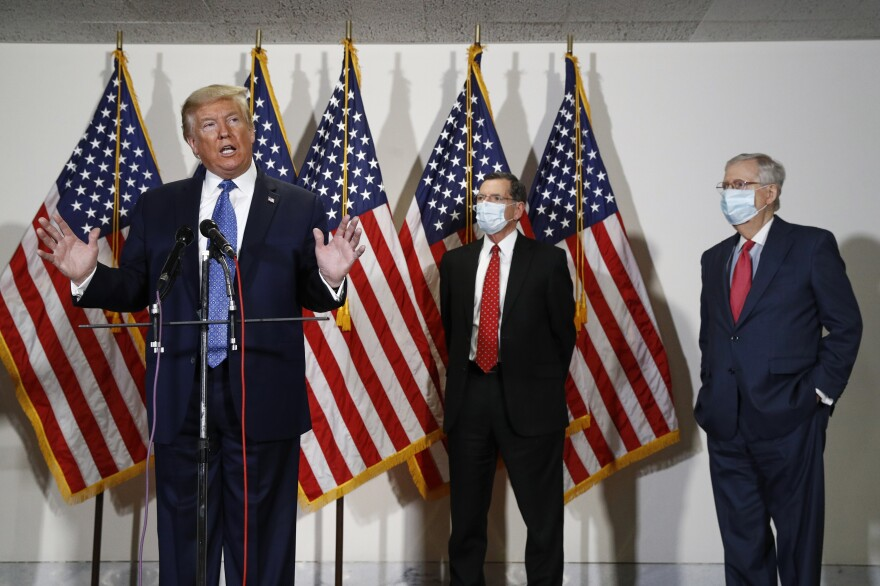 President Trump speaks to reporters May 19 after meeting with Senate Republicans at their weekly luncheon on Capitol Hill. Sen. John Barrasso, R-Wyo., and Senate Majority Leader Mitch McConnell stand at Trump's side.