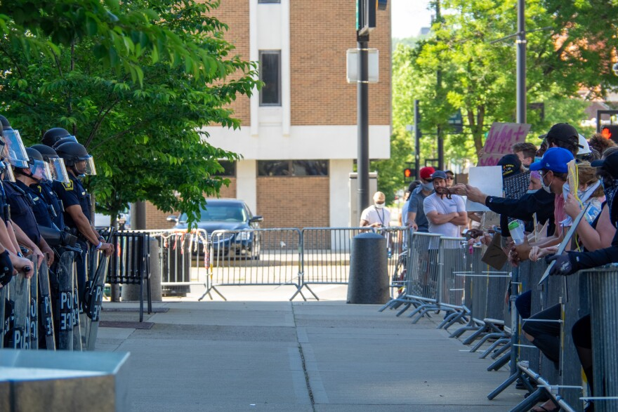 Cincinnati Police Department officers in full riot gear stand across the sidewalk and barricade from protestors as demonstrators continue to rally and protest the murder of George Floyd, Tuesday, June 2, 2020, in Cincinnati.