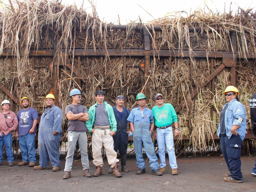 Some of the remaining workers at the mill stand in front of the last hauler truck of Hawaiian sugar cane.