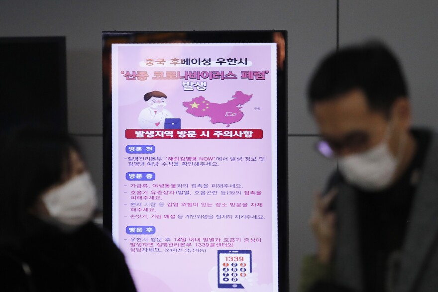 A poster warning about coronavirus is seen as passengers wear masks in a departure lobby at Incheon International Airport in Incheon, South Korea, on Monday.
