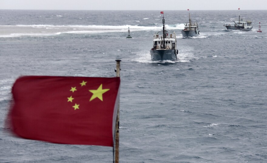 China is currently involved in several disputes with its neighbors over small islands, many of them uninhabited. Here, Chinese fishing boats sail off the island province of Hainan in the South China Sea in July.