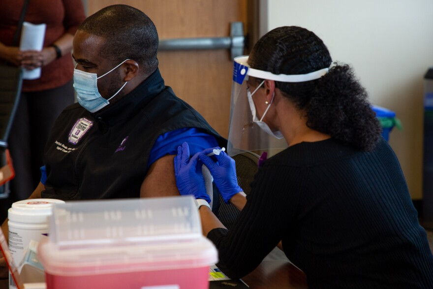 A nurse wearing gloves and a face shield administers a shot to a nurse who works on the COVID-19 team at Parkland Hospital.