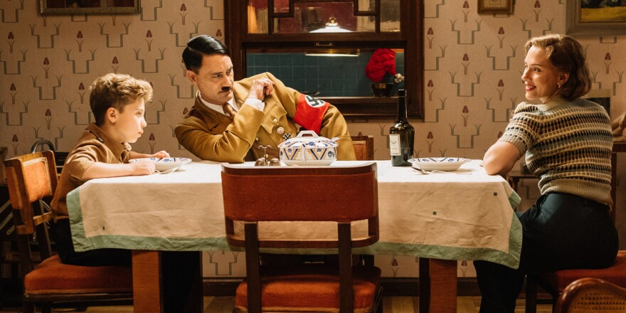 L-R: Jojo (Roman Griffin Davis) has dinner with his imaginary friend Adolf (writer/director Taika Waititi), and his mother, Rosie (Scarlet Johansson) in <em>Jojo Rabbit.</em>