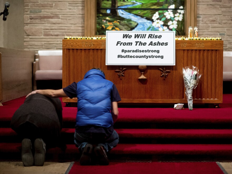 Mourners pray for the victims of the Camp Fire during a vigil Sunday in Chico, Calif. The wildfire killed dozens of people and effectively wiped the entire town of Paradise off the map.