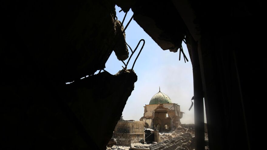 """The ravaged Great Mosque of al-Nuri, as seen through rubble in the Old City of Mosul on Thursday. Iraqi forces say they've recaptured the landmark, where ISIS leader Abu Bakr al-Baghdadi declared the group's """"caliphate"""" in 2014."""