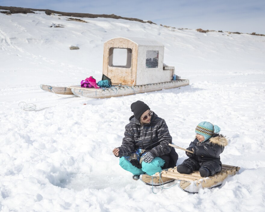 Clara Itturligaq teaches her son Spencer, who is younger than 2, how to ice fish for arctic char at Kuugarjuk Lake near Arctic Bay.