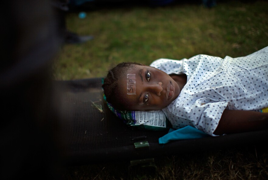 A woman, wearing a tag that identifies her as a transfer patient to the USNS Comfort, waits for a helicopter evacuation in a staging area in front of the National Palace in Port-au-Prince on Jan. 21, 2010.
