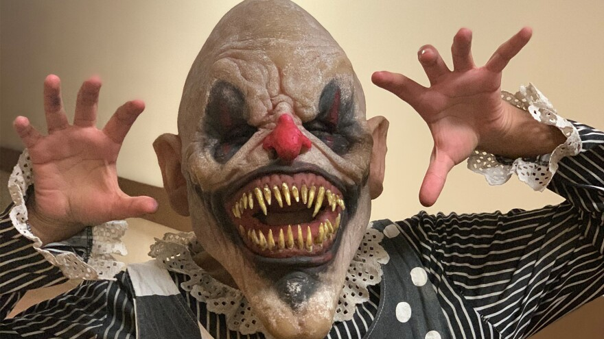 An actor poses wearing a red-nosed, black-eyed evil clown mask.