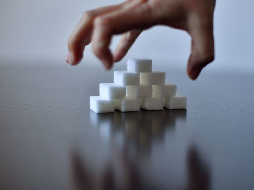 "A girl's hand reaches for sugar cubes. ""We told people to load up on processed carbohydrates and gave sugary beverages a pass,"" said Dr. David Ludwig on what science got wrong about childhood obesity."