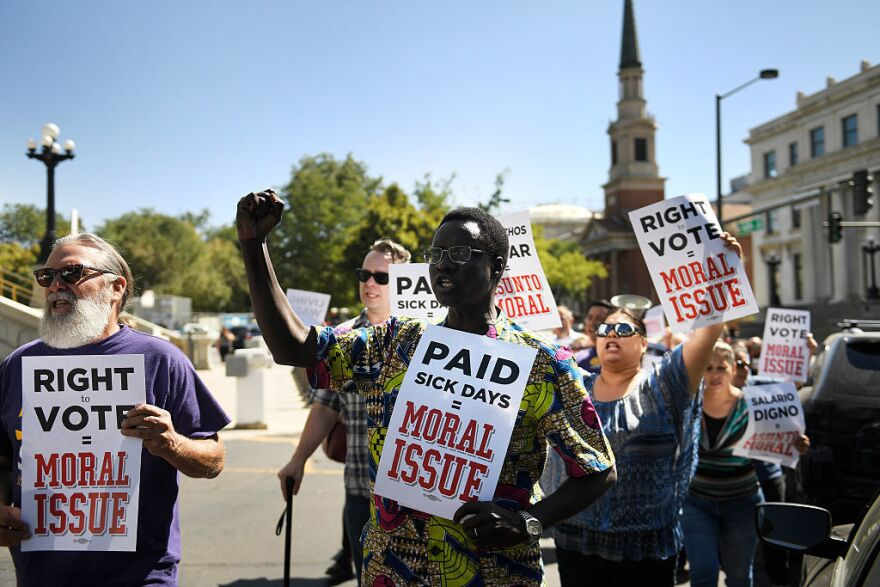 Robert Odeki (center) marches with SEIU Local 105 as the union protested for a minimum wage of $15 an hour outside the Colorado State Capitol in September.