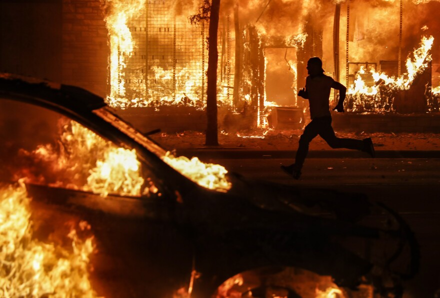 A protester runs past burning cars and buildings on Chicago Avenue, Saturday, May 30, 2020, in St. Paul, Minn.