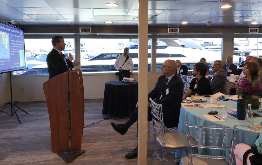 Congressman Ted Deutch sits in the front row as UM, FIU, FAU and NSU researchers present marine research projects to potential investors at the boat show Thursday morning.