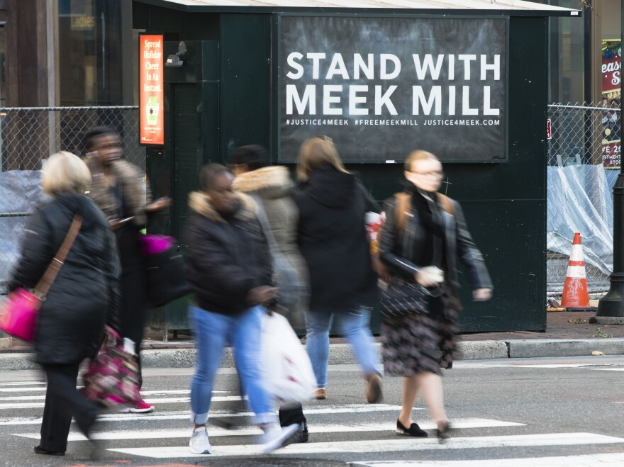 People in Philadelphia walk past a placard posted on a newsstand with a message of support for imprisoned rapper Meek Mill. Mill's imprisonment on a probation violation set off a flurry of legal appeals, criticism of the criminal justice system and rallies in the city last fall.