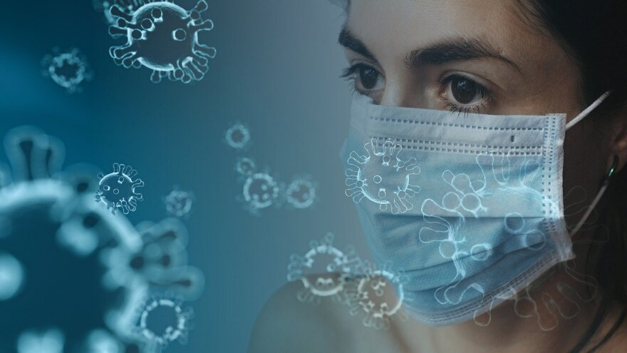 woman in face mask with coronavirus graphic.