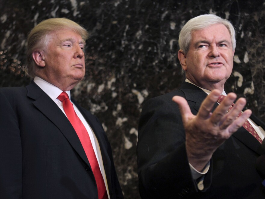 President-elect Donald Trump listens as former House Speaker Newt Gingrich talks to reporters in New York City on Dec. 5. Gingrich suggests that a panel of experts monitor Trump's business conflicts after he takes office.