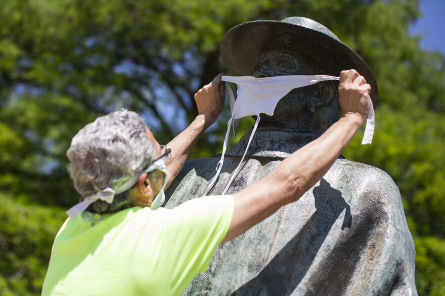 Jeff Levine places a face mask over the statue of Steve Ray Vaughn at Auditorium Shores during the coronavirus pandemic.