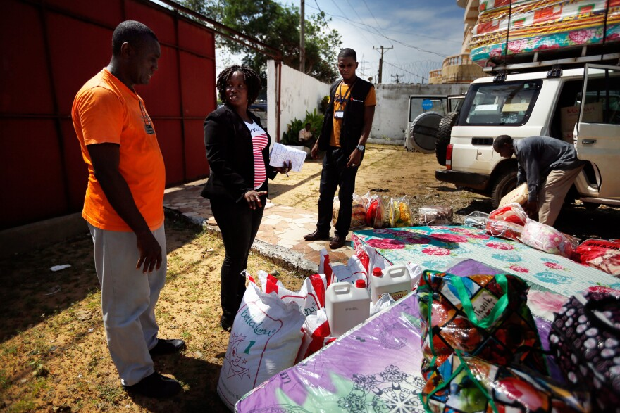 Sienna Wisseh of Liberia's Family Welfare Division (center) directs the packing of supplies that will be given to families adopting or reuniting with children.