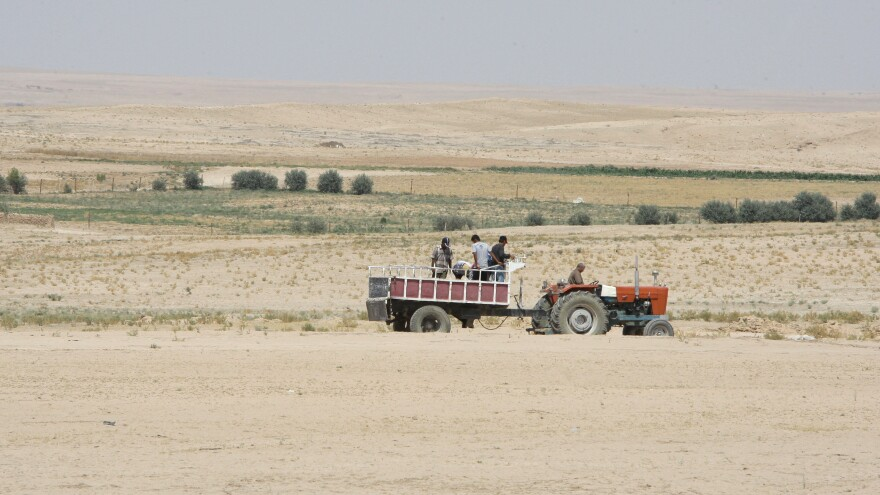 Farmers ride in their tractor in the drought-hit region of Hasaka in northeastern Syria on June 17, 2010.