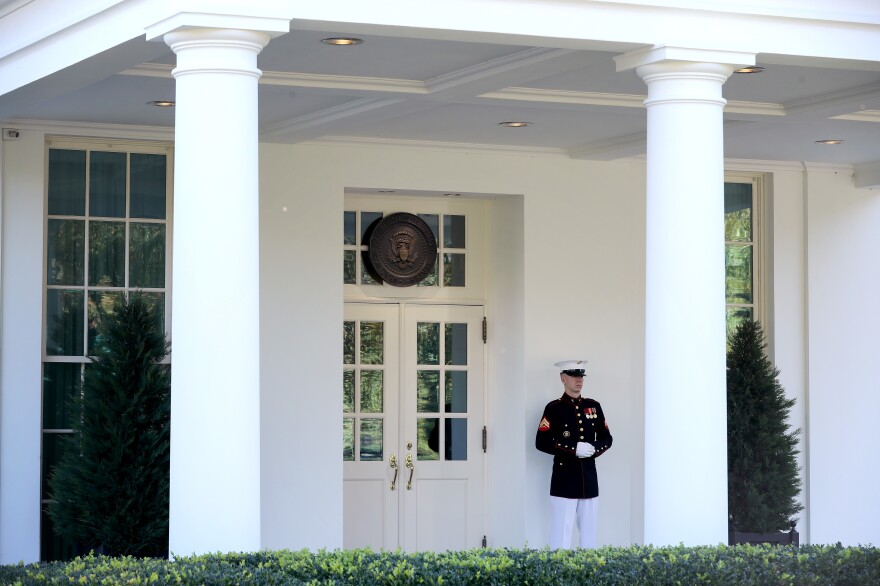 A U.S. Marine stands watch Wednesday outside the doors of the White House West Wing. According to the White House, President Trump was in the Oval Office on Wednesday afternoon, even as he continues to be monitored for COVID-19.