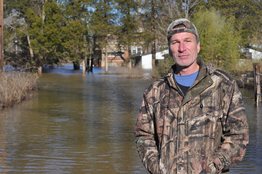 Mark Steinke stands outside his home. On Friday, the driveway was still underwater.