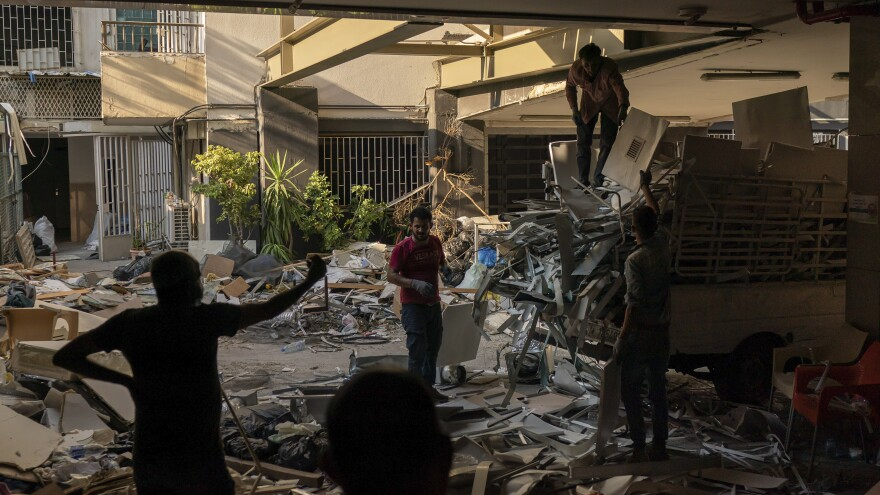 "Workers remove debris from a hospital that was heavily damaged in last month's explosion in Beirut. Lebanon's interim health minister, Hamad Hasan, told local media last month that the health system was ""on the brink"" of being overwhelmed because of the needs of blast victims and COVID-19 patients."