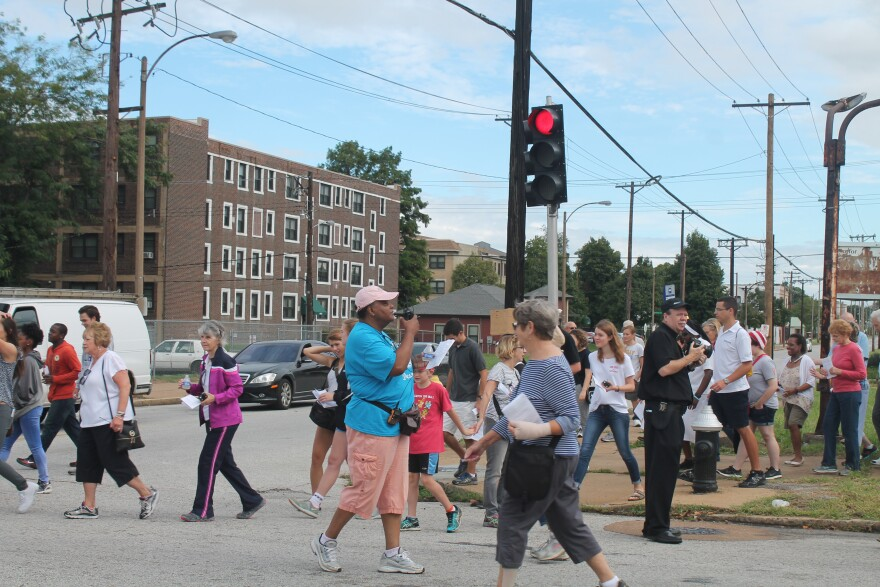 "Event organizer Joyce Jones leads people literally across Delmar Boulevard at Sarah Street as part of the symbolic ""Crossing the Delmar Divide"" pilgrimage on Saturday."