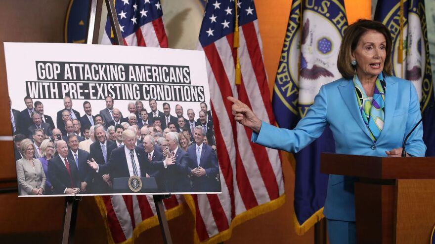 Democratic Minority Leader Nancy Pelosi, D-Calif., speaks about health care as she points to a picture of President Trump with House GOP members during her weekly news conference on Capitol Hill in June.