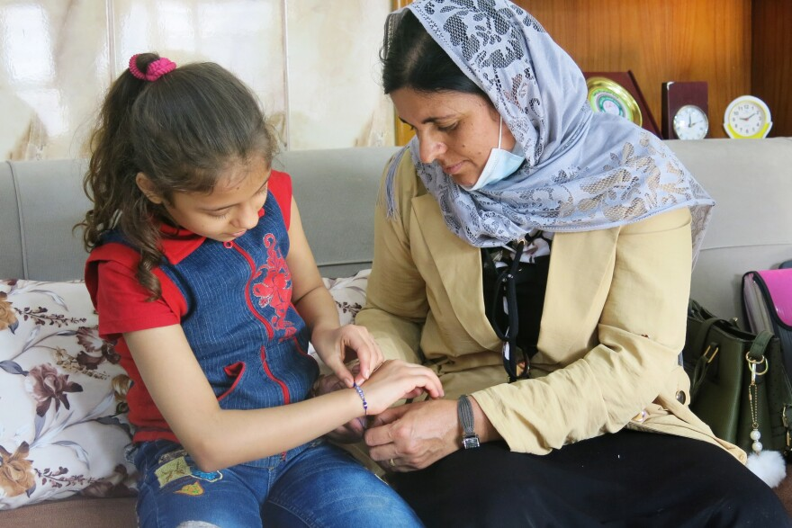 Kamo Zandinan sits in a Mosul orphanage with the 10-year-old she believes is her daughter Sonya, admiring the blue bead bracelet Zandinan has given her. Zandinan is waiting for the results of a DNA test to determine whether the girl, who has been raised by an Arab family, is hers.