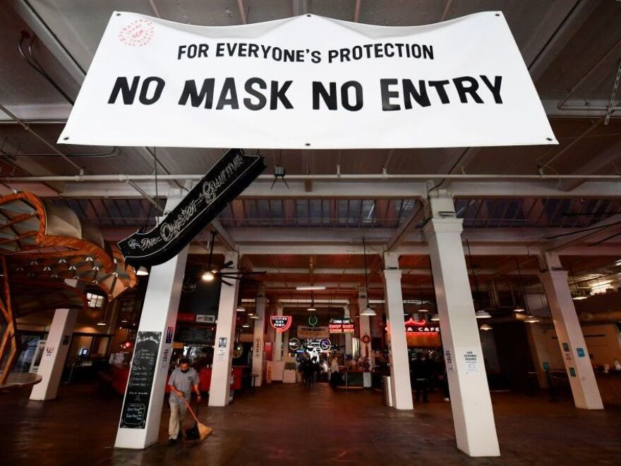 A sign reminds people to wear face masks at an empty Grand Central Market in November in Los Angeles, California. Los Angeles has urged citizens to stay home since early December to slow its outbreak. Stay-home orders can help control a coronavirus surge.