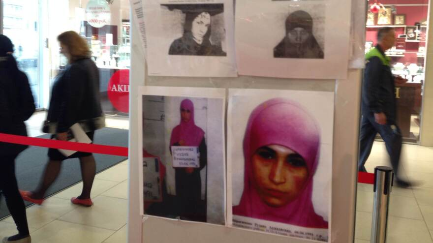Shoppers at a department store in Sochi, Russia, pass an information banner with photos of suspected terrorists wanted by police. The color photo shows Ruzanna Ibragimova, the 22-year-old widow of an insurgent. Police say she has been spotted in recent days in central Sochi.