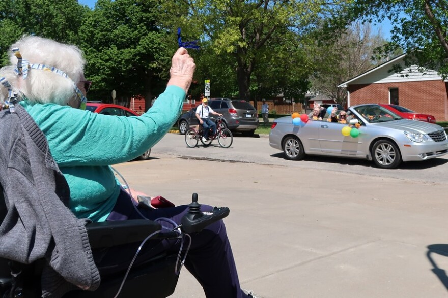 Rosie Ramsey, a Bethany resident, waves at her daughters in a silver convertible during one of the parades that families have held around the building. (Photo courtesy of Jennifer Cantrell)