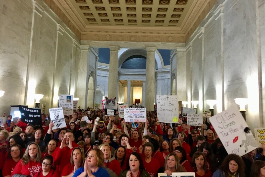 Thousands of teachers rally at the state Capitol in Charleston, W.Va. Teachers went on strike over pay and benefits.