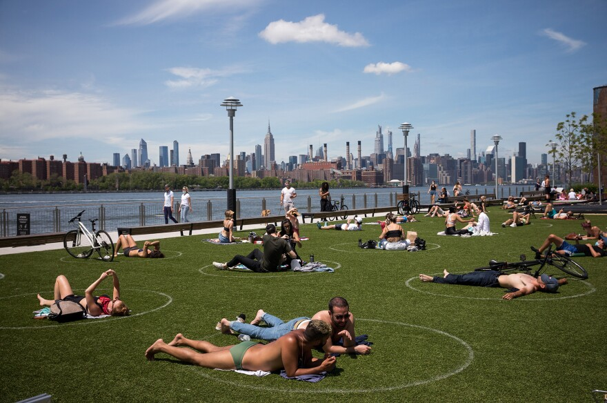"People rest inside social distancing markers at Domino Park in the Brooklyn borough of New York in late May. Stay-at-home orders in New York helped to lower the state's ""reproduction number,"" which estimates how many people one sick person could infect with the coronavirus."