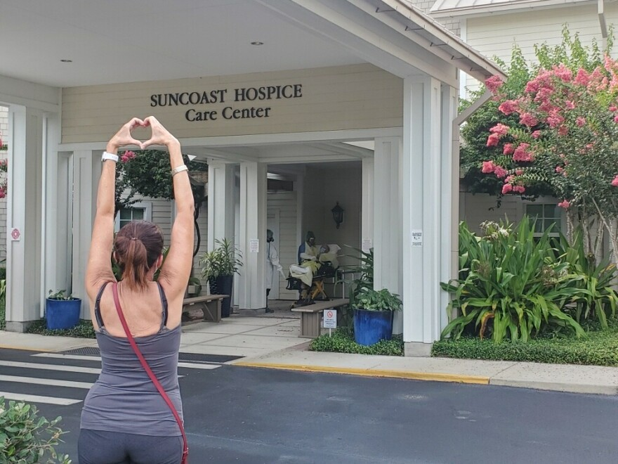 Davonne Irion communicates her love for her father, John Marsh, using her hands outside of the Suncoast Hospice Care Center.
