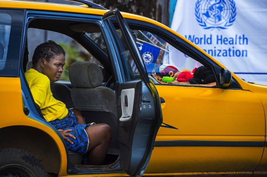 A pregnant woman waits for help in a cab outside John F. Kennedy hospital in Monrovia, Liberia, in September. Then closed, the hospital's maternity ward reopened in October and is now one of the few places in Monrovia delivering babies.