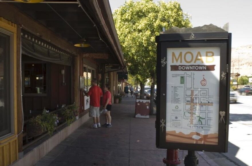 A sign with a map of downtown moab and two people looking in a shop window.